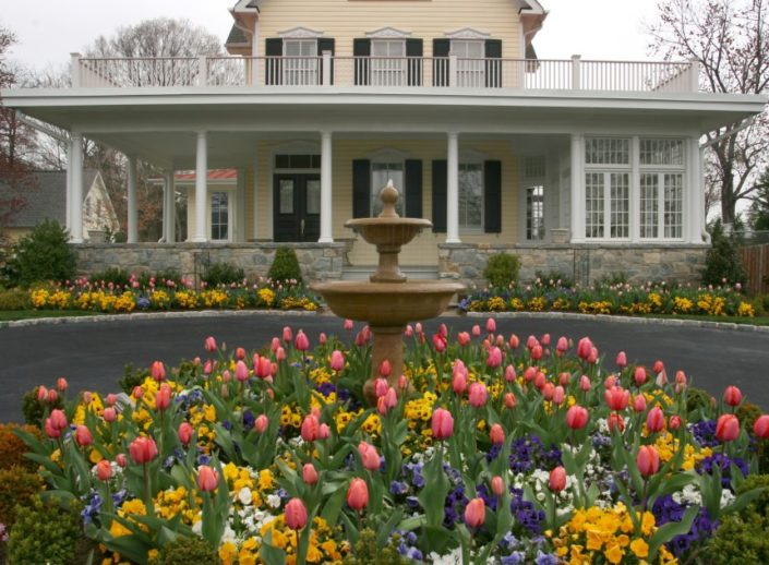 Yellow Home with Porch, Fountain, Tulips