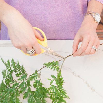 """Tips for arranging your roses: Trim any broken leaves and branches that are too low on the stems of your greens. Trim the ends of your green stems at least ¼"""" on a steep angle. Cutting at a steep angle creates more surface area through which the cells can draw in water. Place your greens in the vase within eight seconds of trimming (if you wait too long the cells fill with air and prevent the stem from drinking)."""