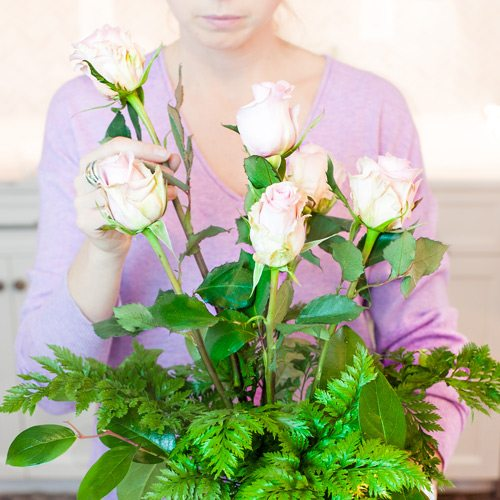 Tips on arranging your roses: Select the next five tallest stemmed roses. Trim them to be slightly shorter (about an inch to two inches) than your center rose, trimming as you did your center rose. Trim all five roses one at a time, to the same length, placing them in water within the eight second window. Place these roses in the vase by aiming their stem ends toward and around the center rose. These roses should be spaced equally apart.