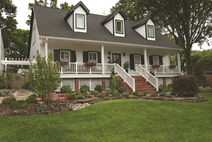 White and Brick With Deciduous and Perennial Foundation Plantings