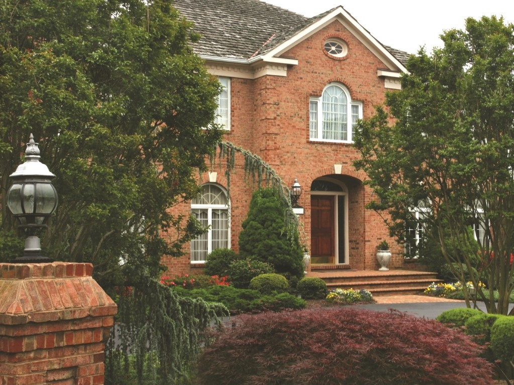 Evergreen plantings in front of brick home